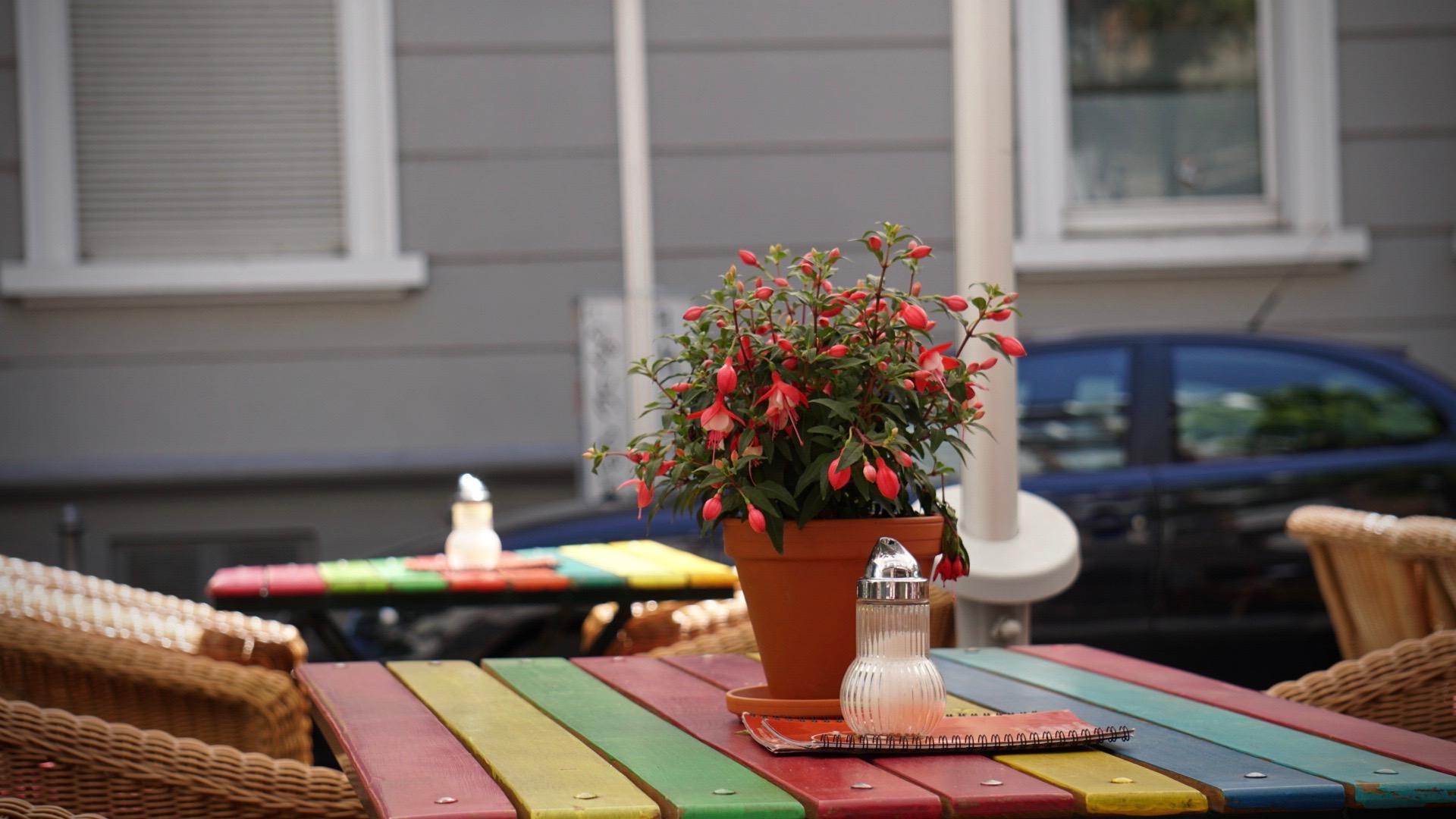 Die bunten Tische vor dem Restaurant verlocken zum Verweilen - egal, ob im Schatten oder in der Sonne
